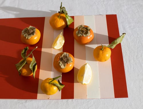 Healthy assorted citruses and persimmons fruits placed on paper sheets on table