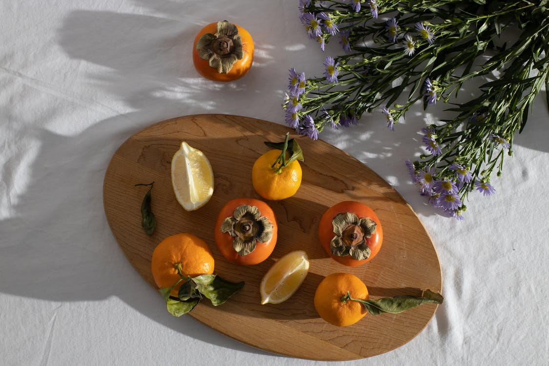 Top view of healthy ripe whole persimmons and tangerines placed on wooden cutting board with lemon slices near bunch of Aster amellus herbaceous flowers