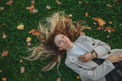 From above of charming female in trendy clothes relaxing on field with closed eyes in autumn park