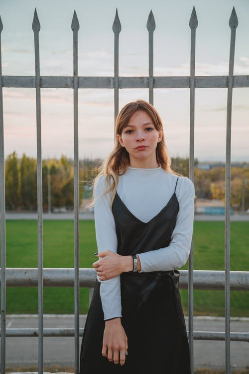 Confident young woman standing against fence