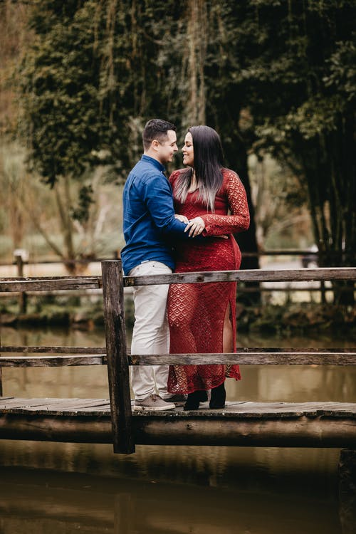 Diverse couple embracing on old wooden bridge