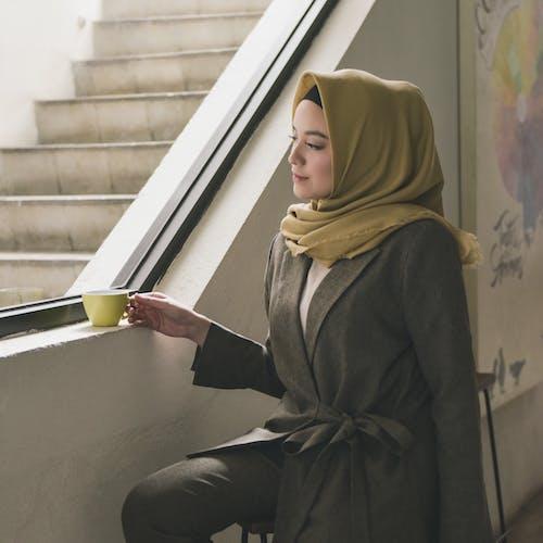 Woman in Black Coat and Yellow Hijab Sitting on Window