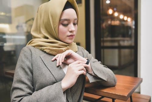 Woman in Gray Coat and Brown Hijab Sitting on Brown Wooden Chair