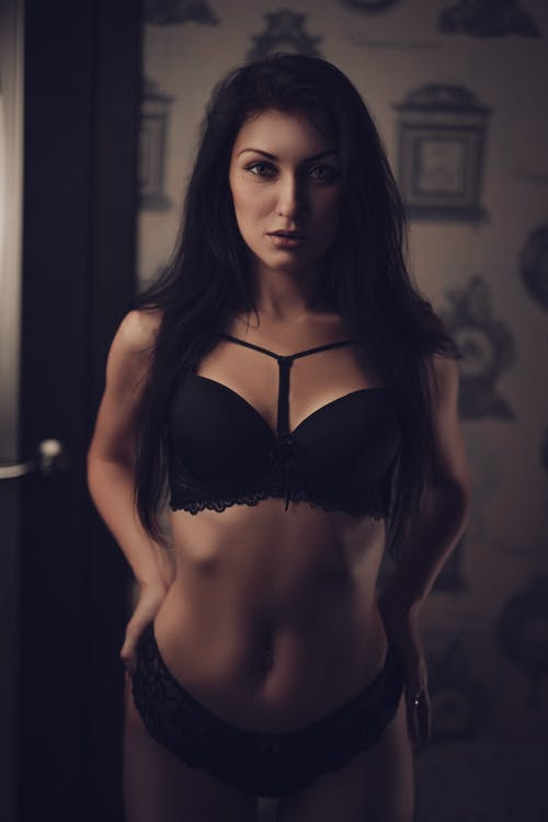 Seductive fit female wearing black lace underwear touching buttocks and looking at camera while standing in dark room