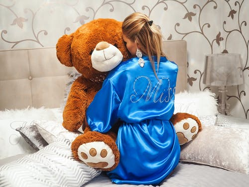 Woman Wearing Blue Bathrobe While Hugging Brown Bear Plush Toy