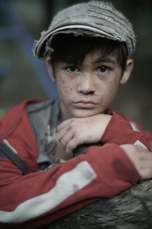 Poor ethnic boy with freckles on street