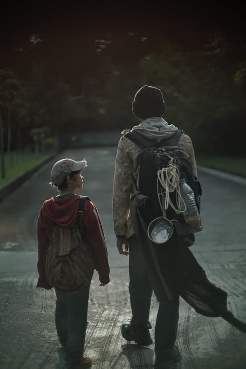 Back view of unrecognizable poor kid and teenager with backpacks walking on urban road in twilight