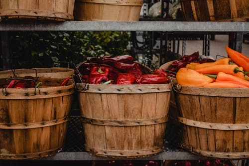 Red and Yellow Bell Peppers in Brown Wooden Bucket