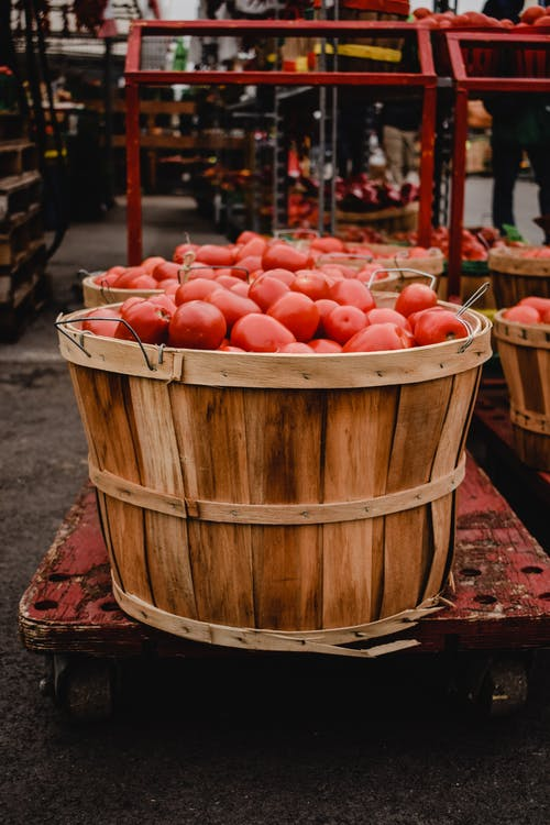 Red Round Fruits on Brown Wooden Bucket