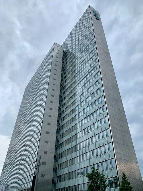 From below of contemporary minimalist multistory building with glass mirrored windows located on city street against cloudy sky