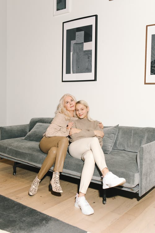 Mother And Daughte Sitting Close To Each Other On A Gray Couch
