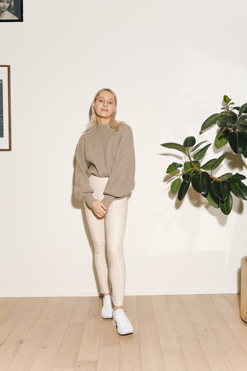 Woman in Gray Long Sleeve Shirt and White Pants Standing Beside Green Plant