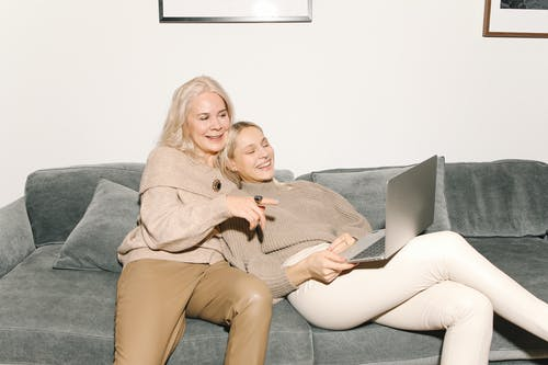Mother And Daughter Smiling While Using A Laptop