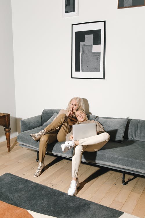 Mother And Daughter Sitting on Gray Couch With A Laptop