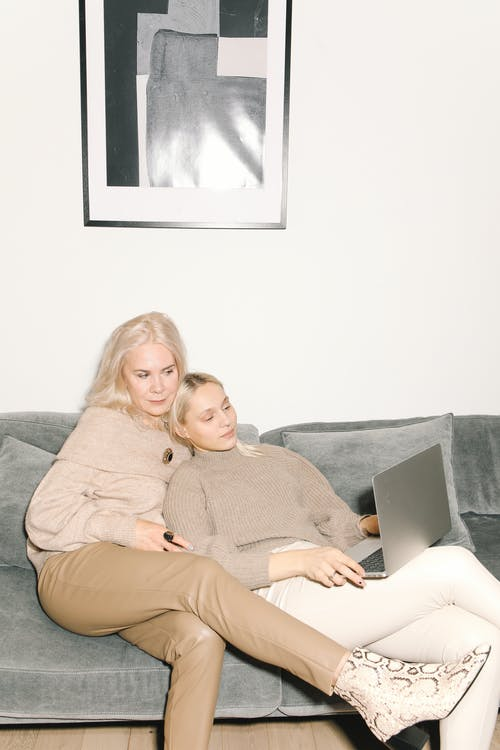 Mother And Daughter Sitting On A Gray Couch Watching Using A Laptop
