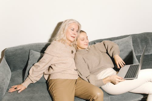Mother And Daughter Sitting On Gray Couch Looking At A Laptop