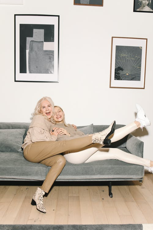Mother And Daughter Sitting On Gray Couch With Legs Raised