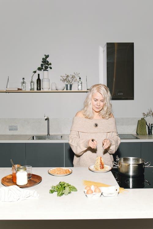 Woman in White Sweater Preparing Spaghetti