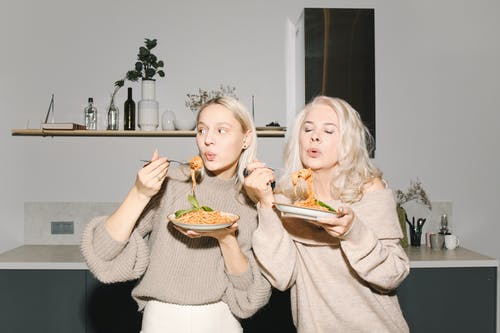 Mother And Daughter Eating Spaghetti