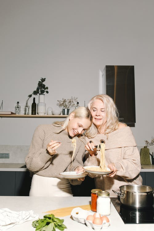 Mother And Daughter Holding Plates With Spaghetti Noodles