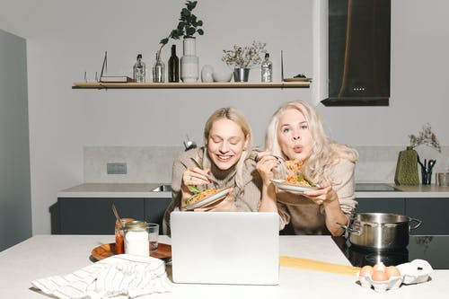 Mother And Daughter Eating Spaghetti in Front of Table With Macbook Air