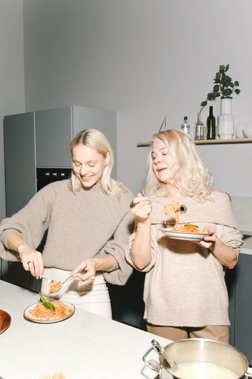 Mother And Daughter Eating Pasta