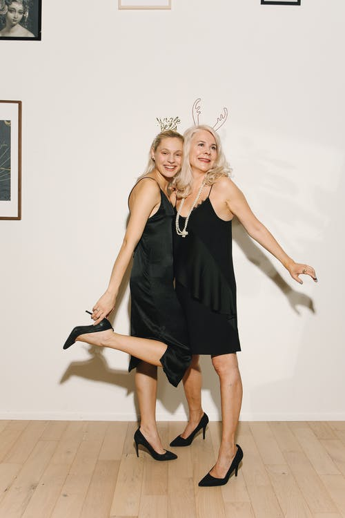 Mother And Daughter in Black Spaghetti Strap Dress Standing and Smiling