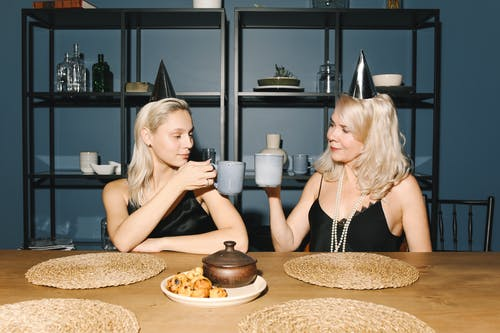 Mother And Daughter Holding Coffee Mugs And Making A Toast
