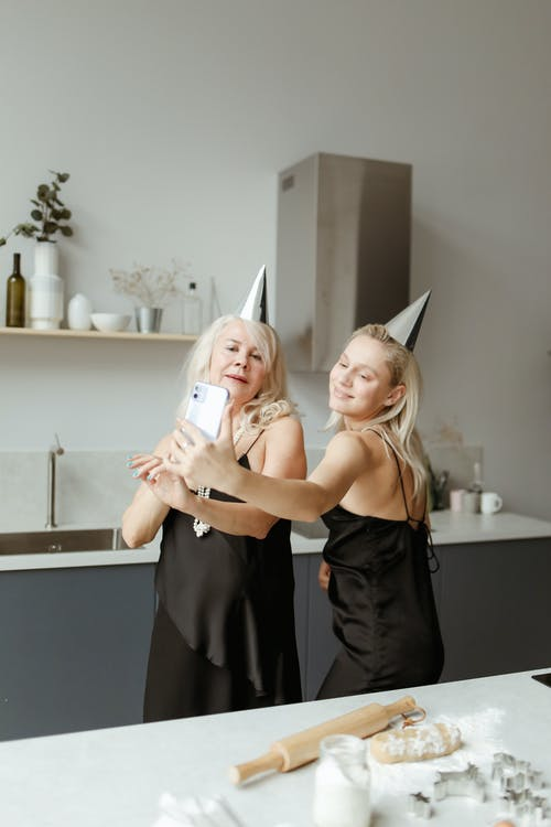 Mother And Daughter Taking Selfie While Cooking