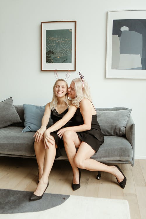 Mother And Daughter in Black Dress Sitting on Gray Couch
