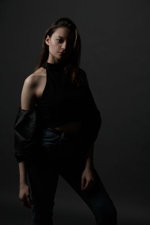 Trendy woman standing confidently in dark studio