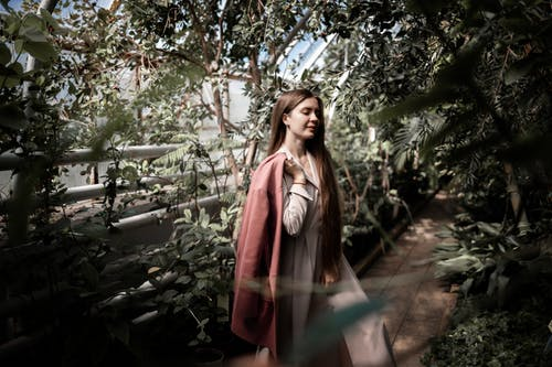 Peaceful woman standing in glasshouse