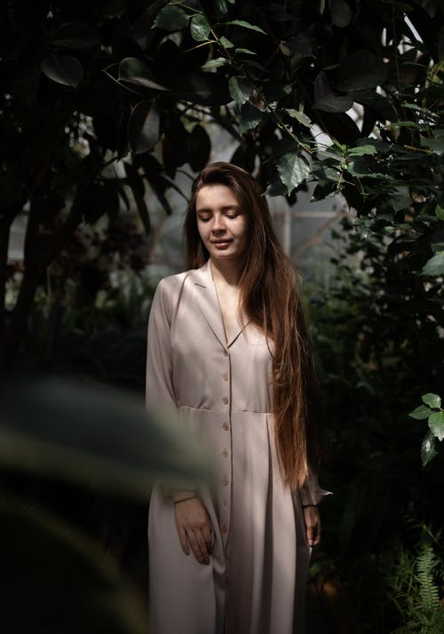 Peaceful female with long dress wearing elegant dress looking down while standing among lush green deciduous plants and bushes in hothouse