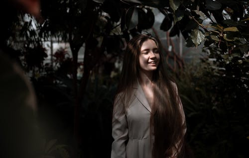 Smiling female with long hair wearing elegant dress looking into distance while standing in botanical garden under shadow of green lush deciduous plants