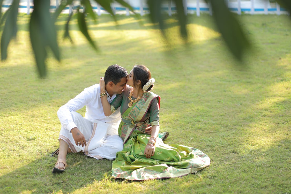 Man and Woman Sitting on Green Grass Field