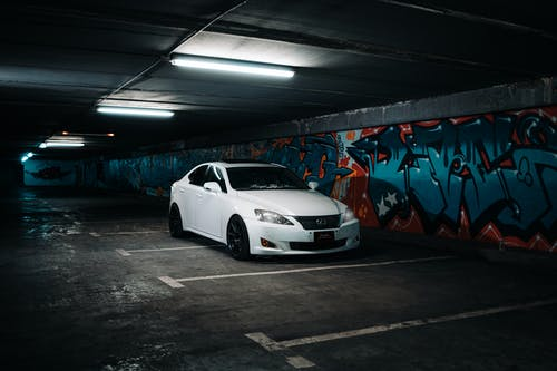 White Car Parked Beside Wall With Graffiti