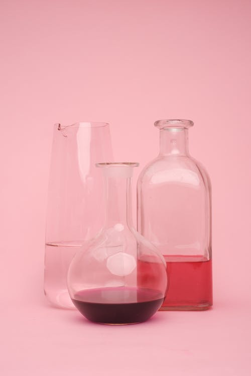 Transparent glass laboratory flasks of various shapes with different chemical liquids placed against pink background