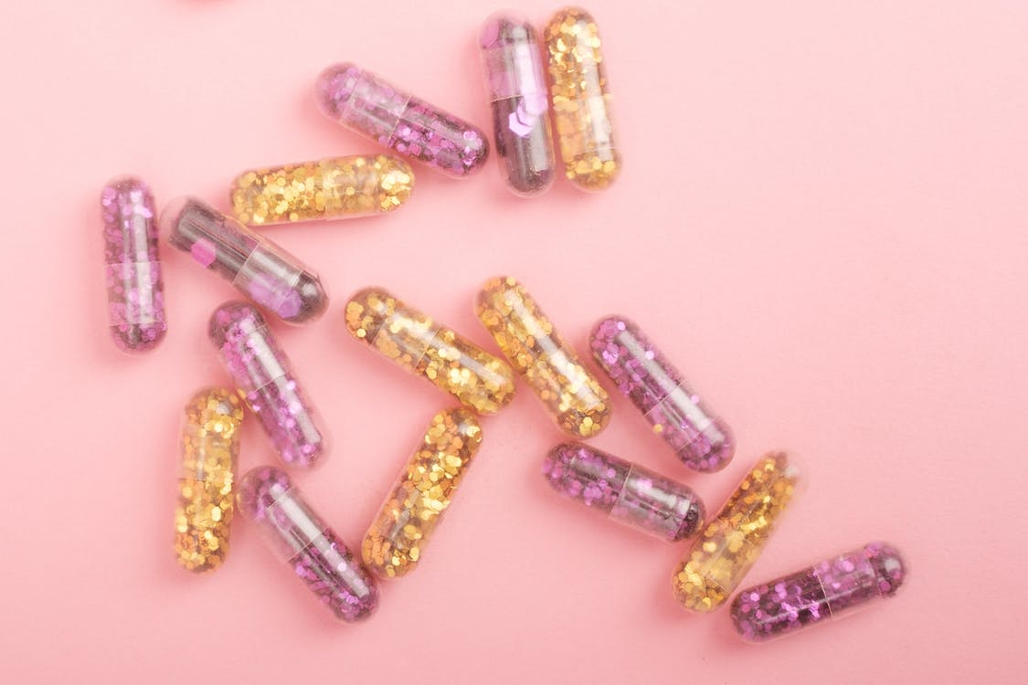Pile of sparkling drug capsules scattered on pink surface