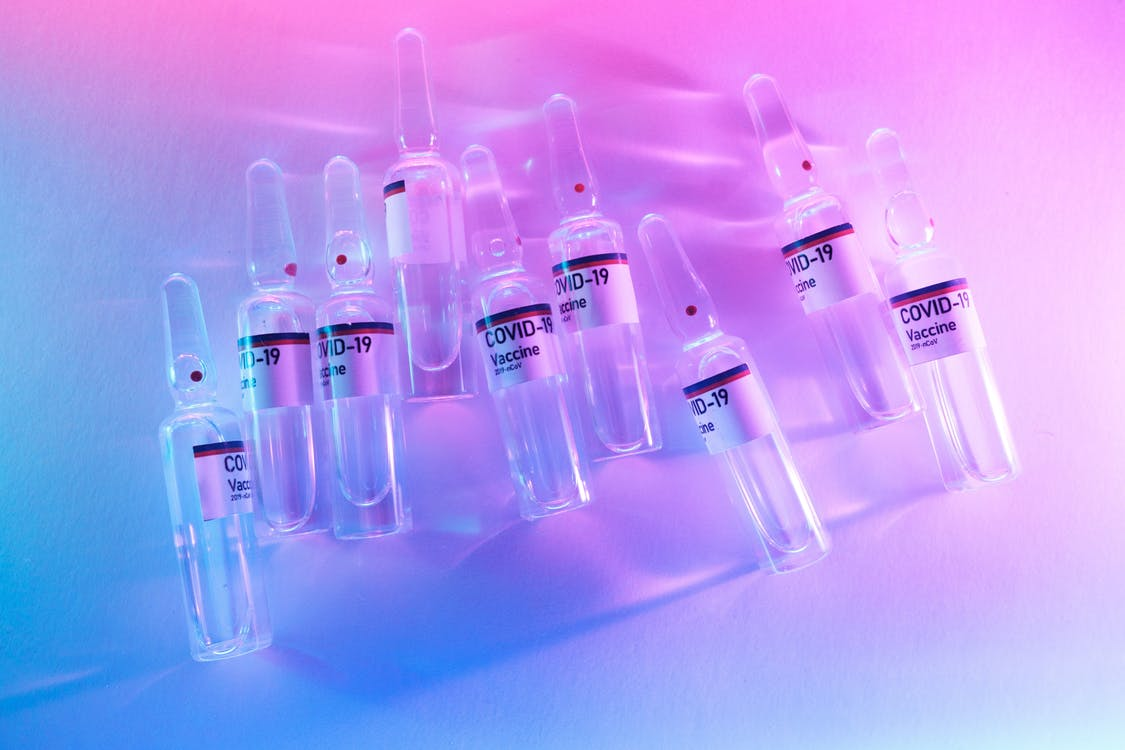 From above pile of doses of COVID 19 vaccine in similar ampoules placed on desk in laboratory with neon lights