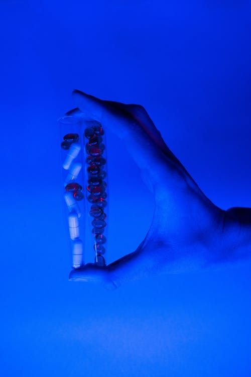 Vials with pills and capsules in ultraviolet light in hand