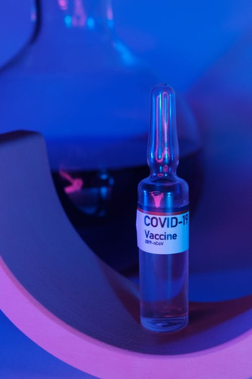 Glass ampoule with vaccine for COVID 19 near flask with fluid in ultraviolet light