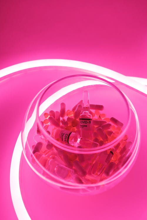 From above of glass bowl filled with pills and ampoules with vaccine for COVID 19 in pink bright neon light