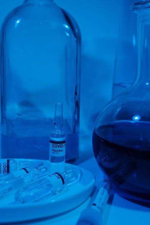 Ampoules with vaccine for COVID 19 near glassware