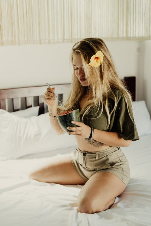 Woman in Black Shirt and White Shorts Sitting on Bed Holding Black Ceramic Mug