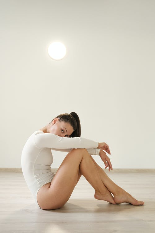 Barefooted slim young woman sitting on floor during dance lesson