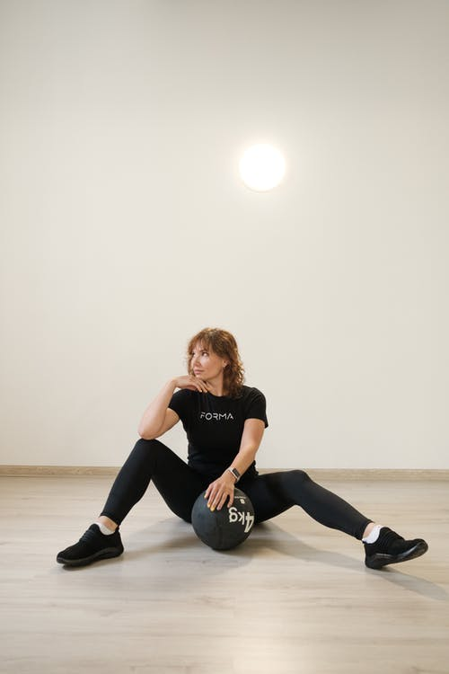 Young fit lady with weight ball resting after training in studio