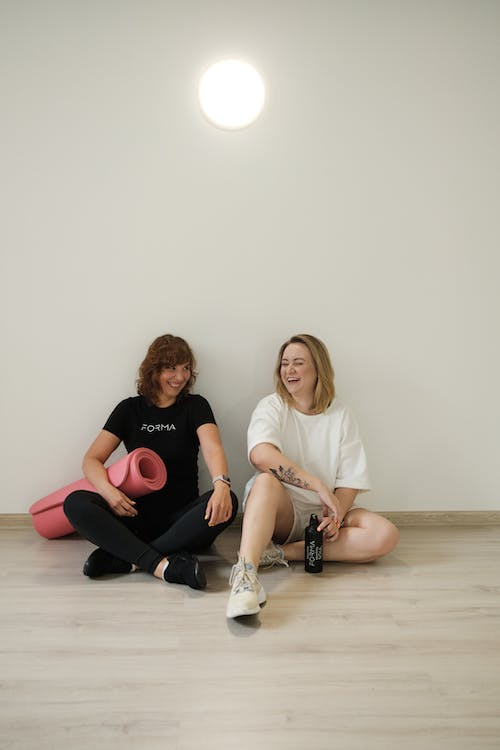 Cheerful young women chatting after workout in gym
