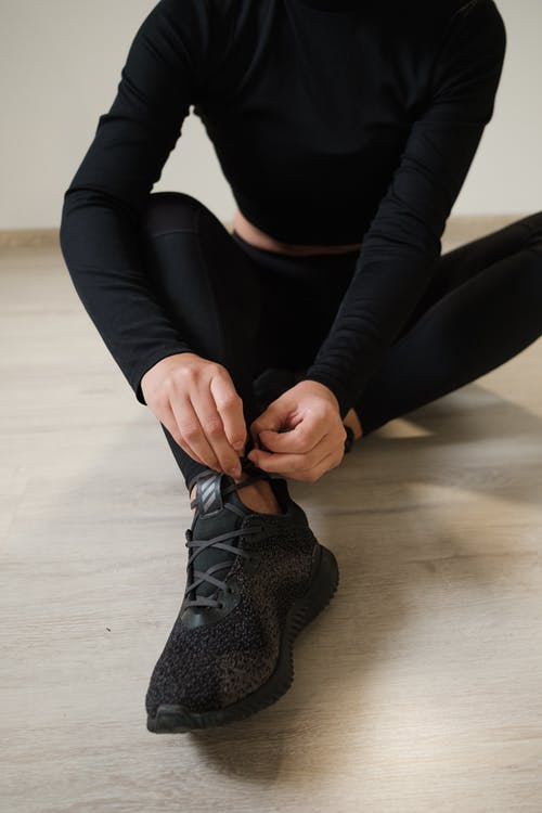 Unrecognizable fit woman tying laces on sneakers in gym