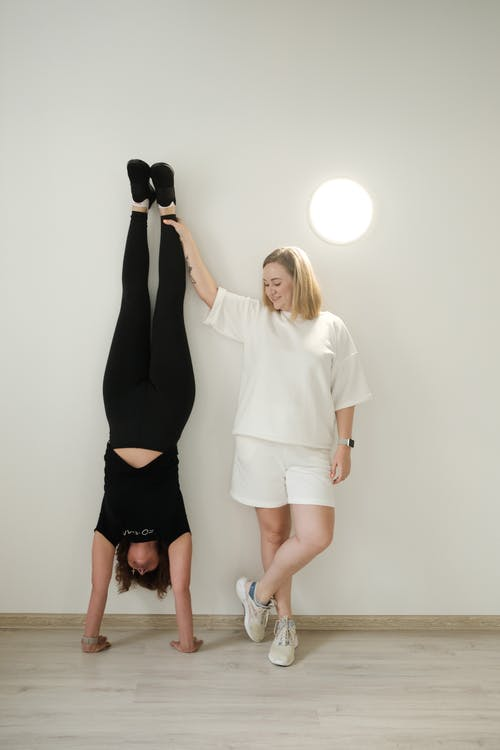 Young woman helping friend during headstand exercise in studio