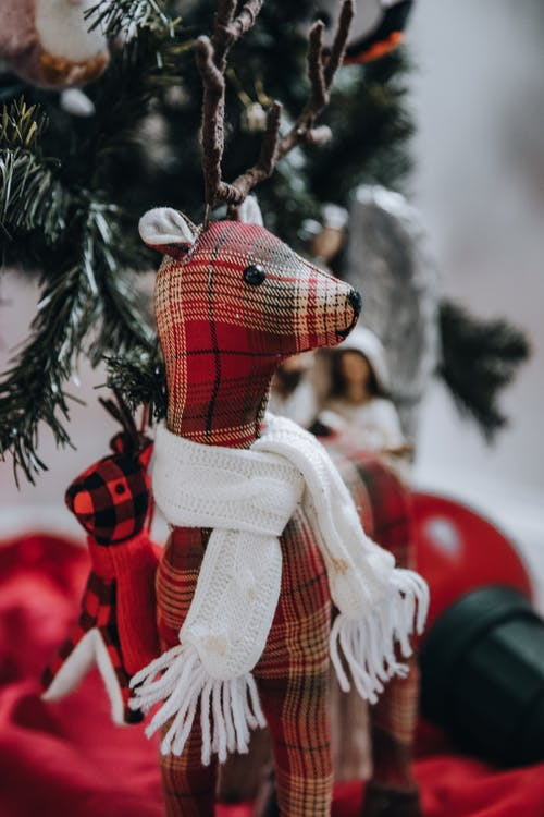 Cute handmade checkered reindeer with scarf hanging on branch of Christmas tree in room on blurred background during holiday celebration